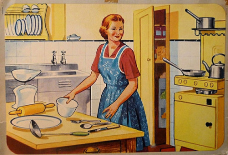 Female smiling with an apron and standing in front of cooking equipment in a kitchen
