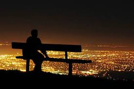 Male sitting on a bench alone in the darkness and staring into the view of lit up buildings in front of him