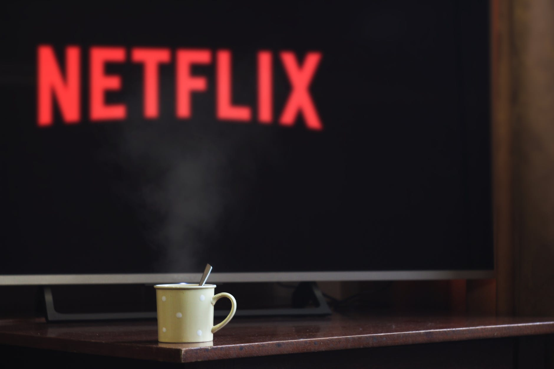 Steaming cup of hot beverage with a wide flat-screen TV showing Netflix logo in the background