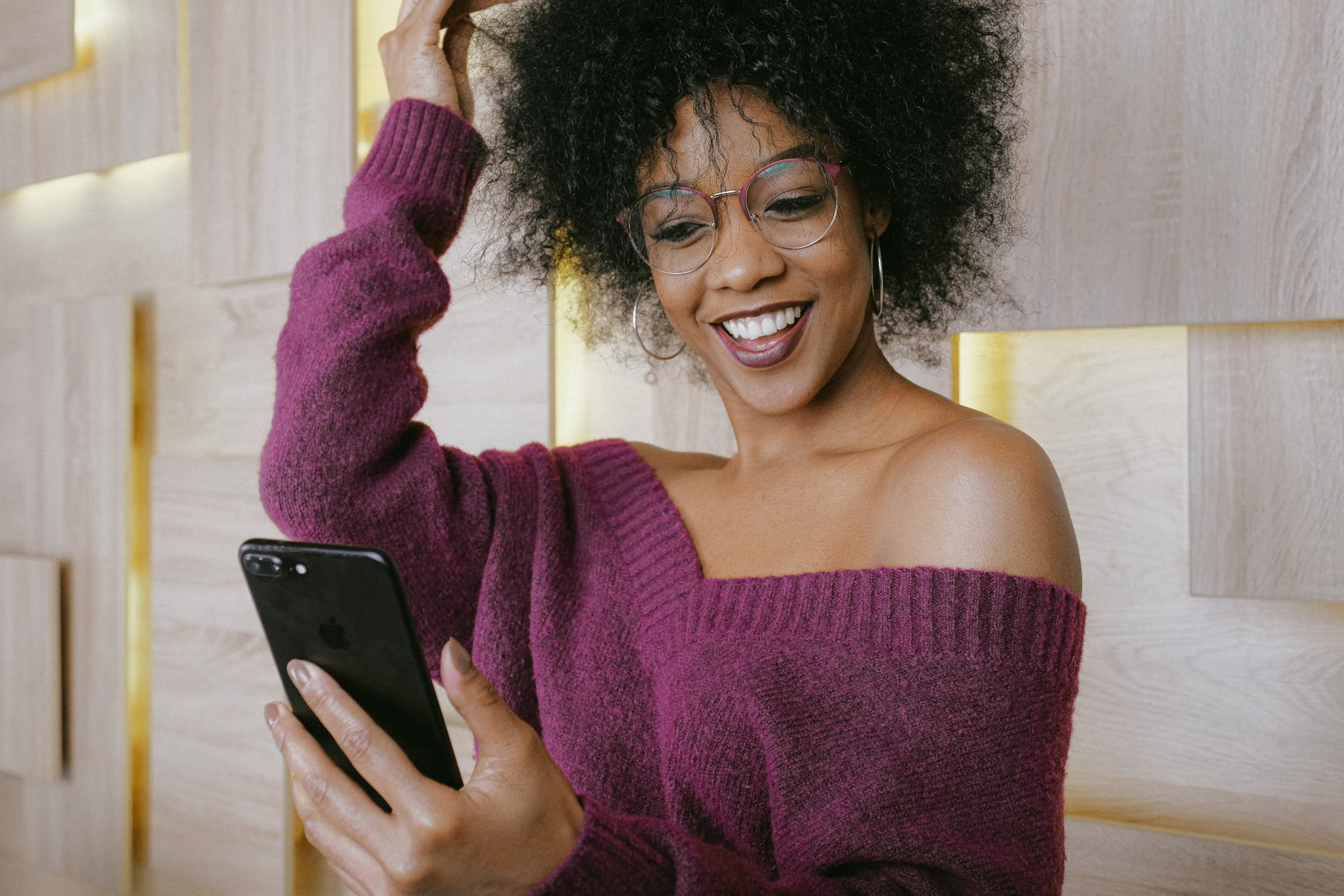 Dark female smiling and holding a phone in front of her