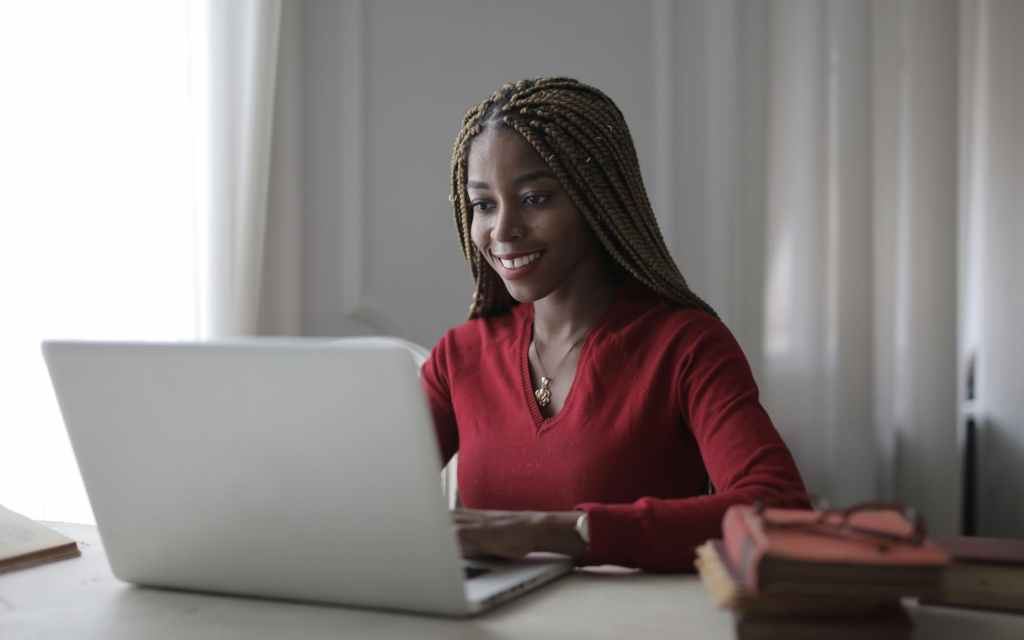 Dark female smiling with a laptop in front of her