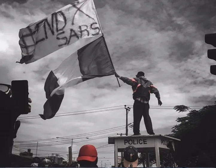 Man standing on top of a mobile police station, waving a white End SARS flag and the Nigerian flag